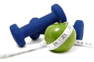 Blue weights, green apple, and tape measure isolated on a white background
